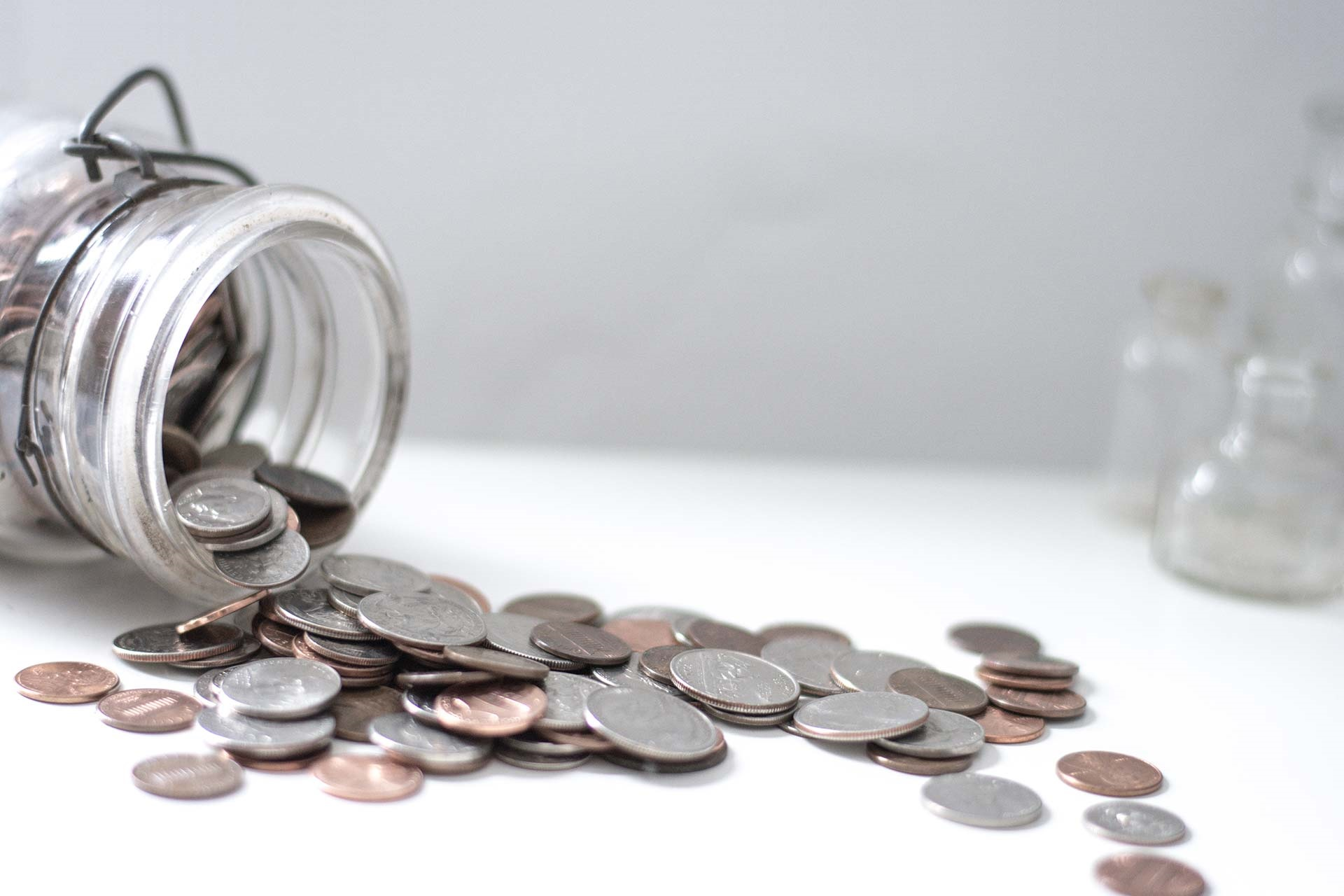 Coins in a jar depict saving money for retirement.